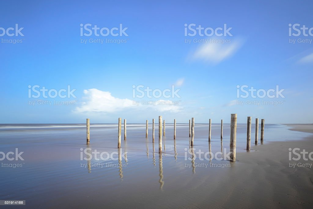Poles at the beach during a beautiful winter day stock photo