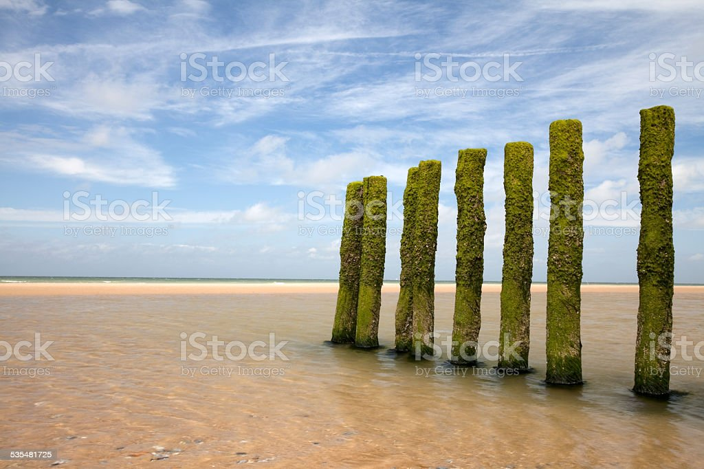 Poles in the sand at low tide stock photo