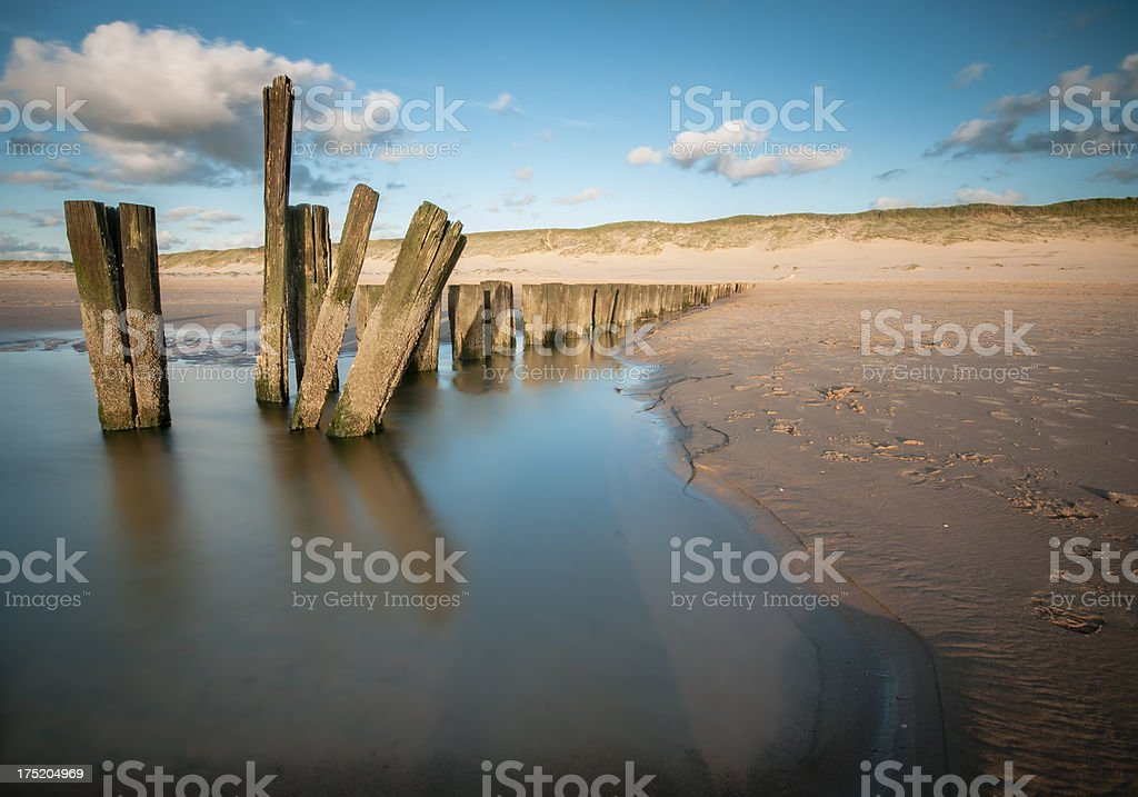 Poles on the beach during sunset stock photo