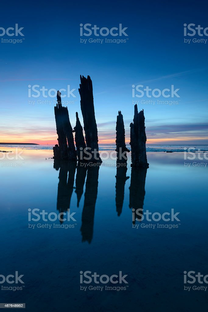 Poles standing in a colorful sunset stock photo