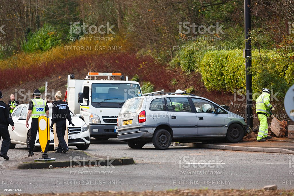 Police and council workers dealing with a car crash stock photo