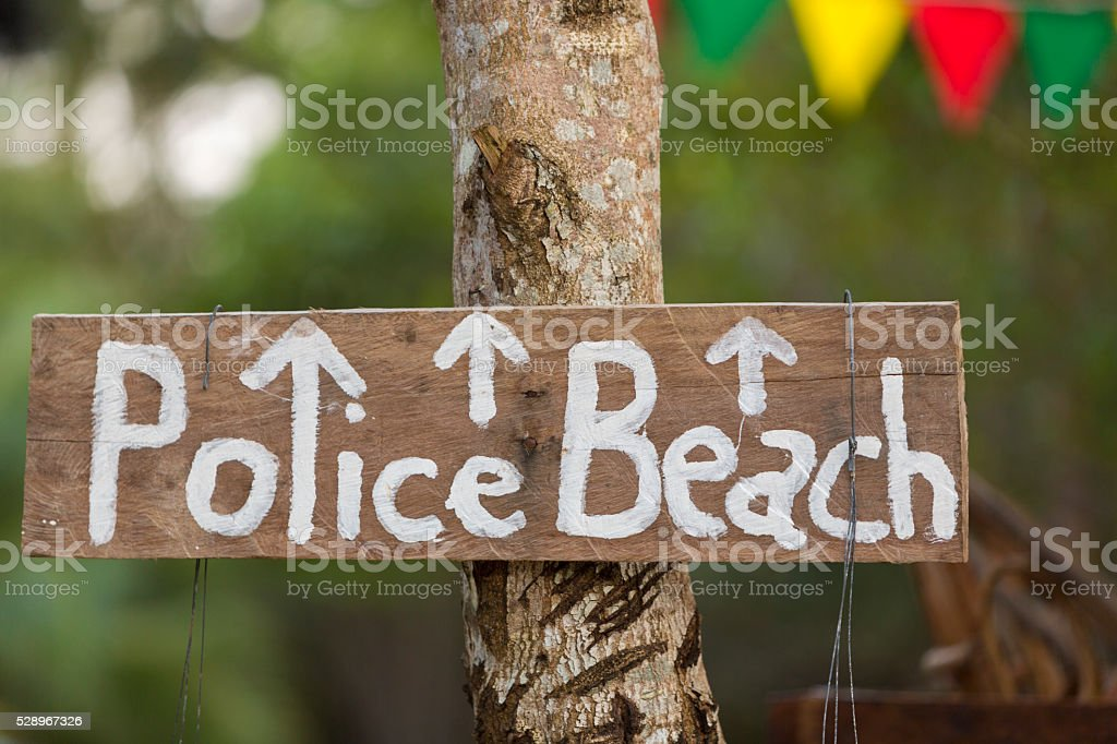 Police beach wooden sign hanging on tree, Koh Rong Island stock photo