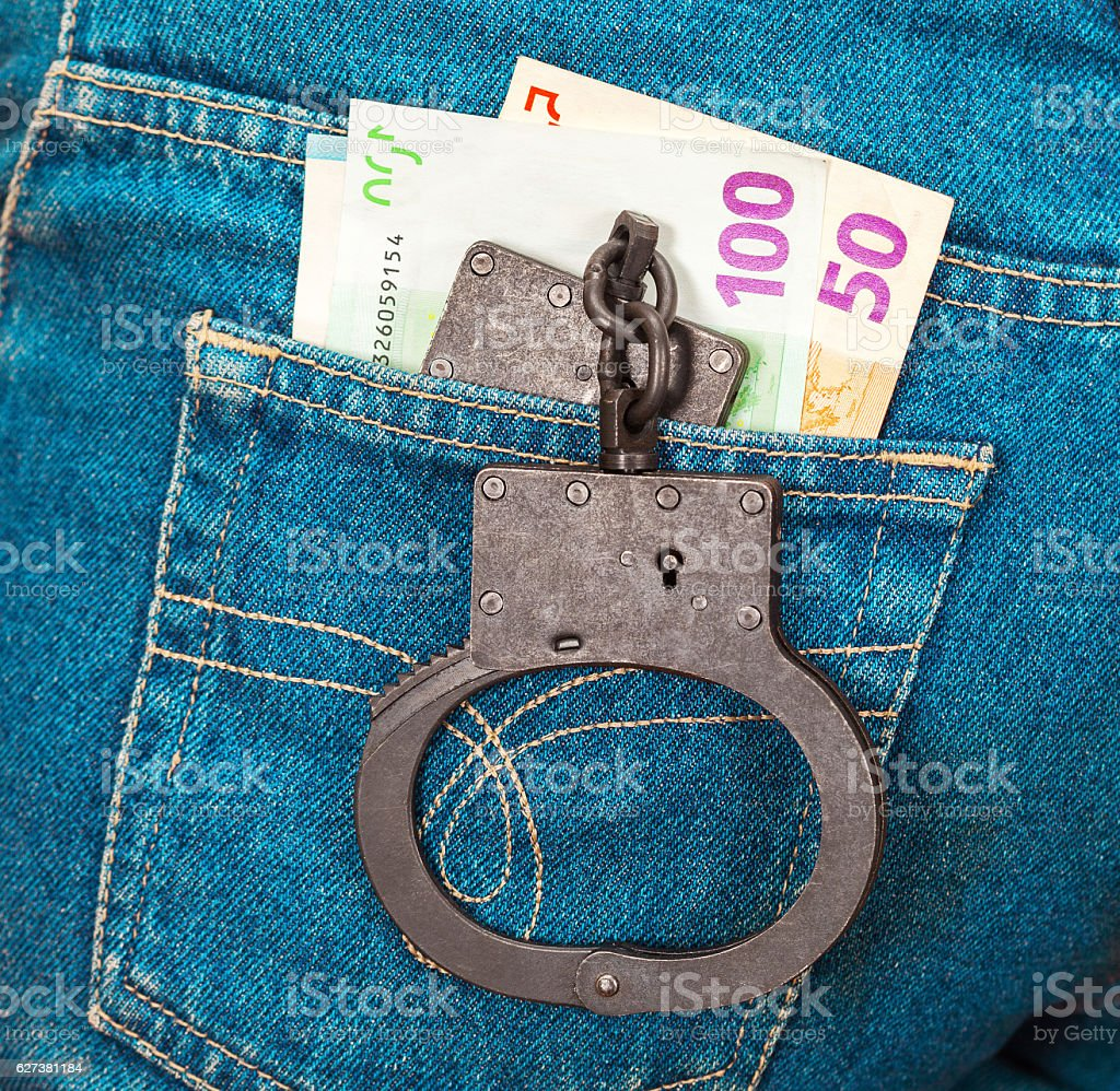 Police black metal handcuffs and euro currency stock photo