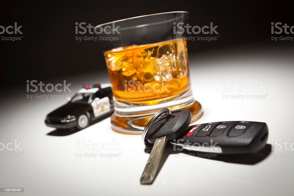 Police car and keys at base of an alcoholic beverage stock photo