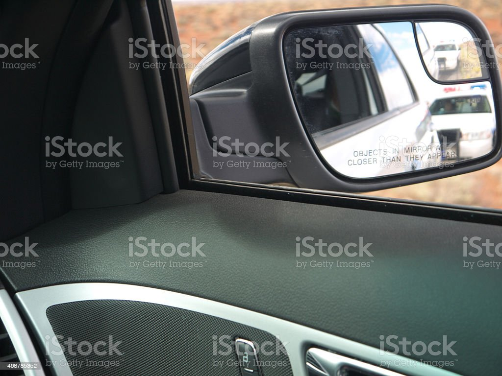 Police car in rear view mirror stock photo