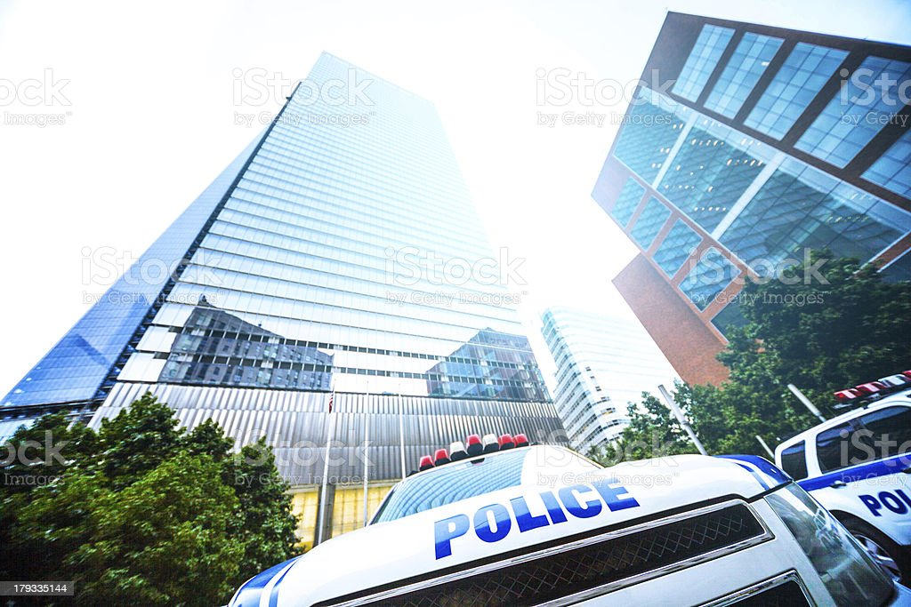 Police car parked under financial skyscraper stock photo