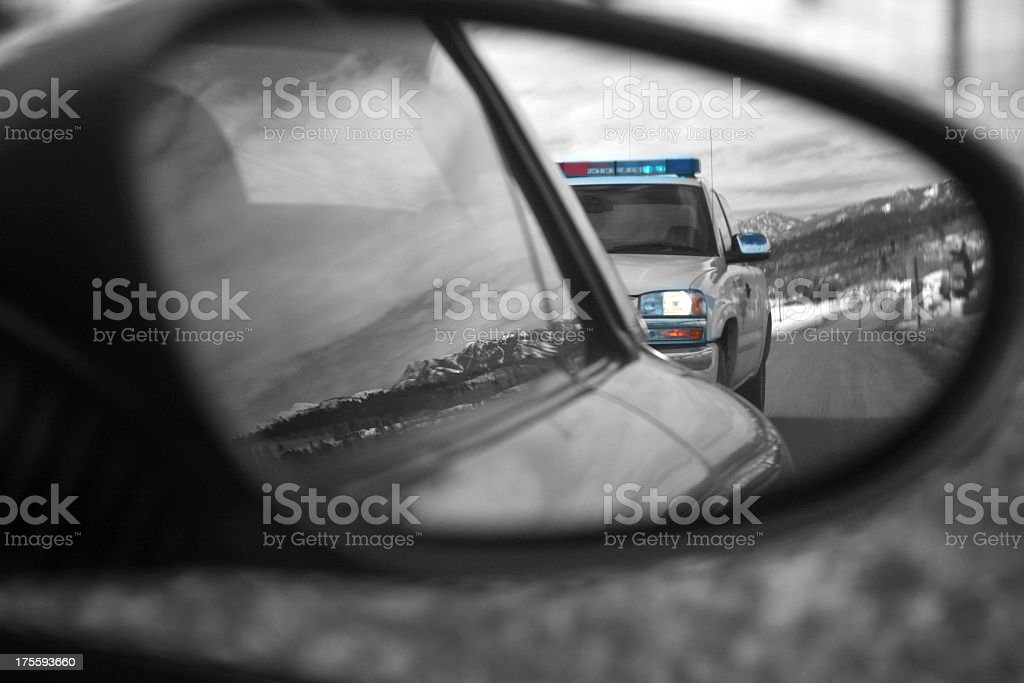 Police car reflected in side mirror of speeding car stock photo