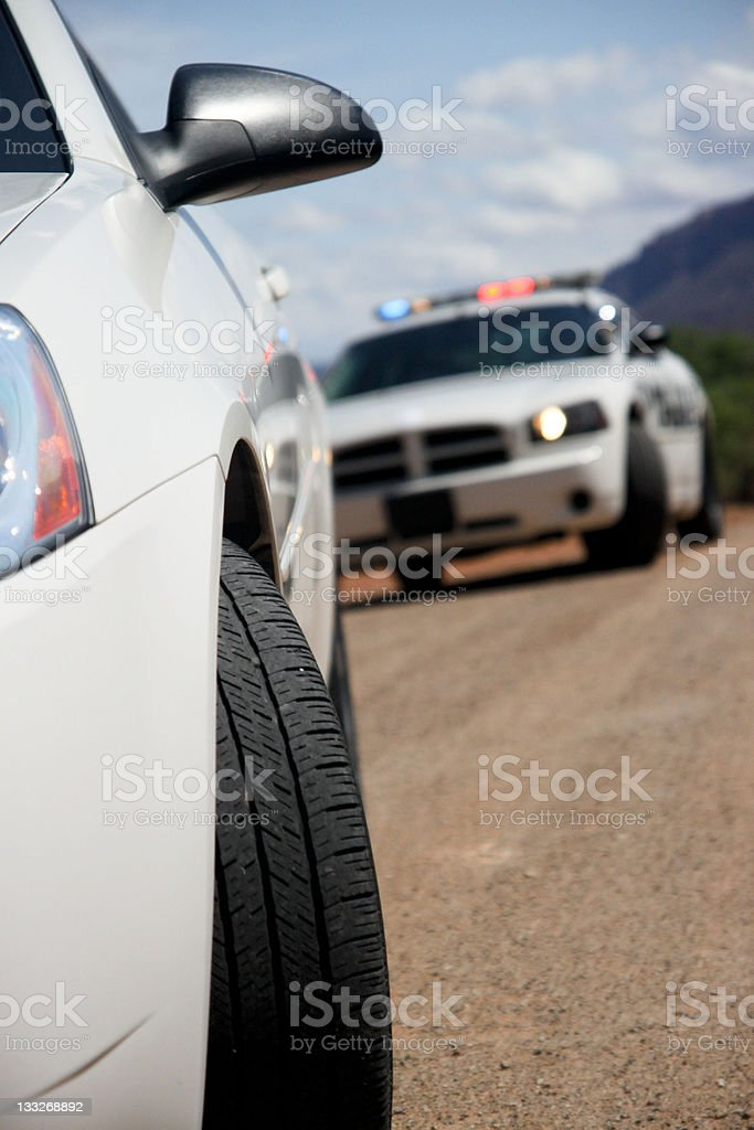 Police car stopping a dodge white car in front stock photo