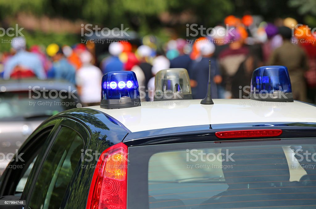police car with blue sirens in the street escorting participants stock photo