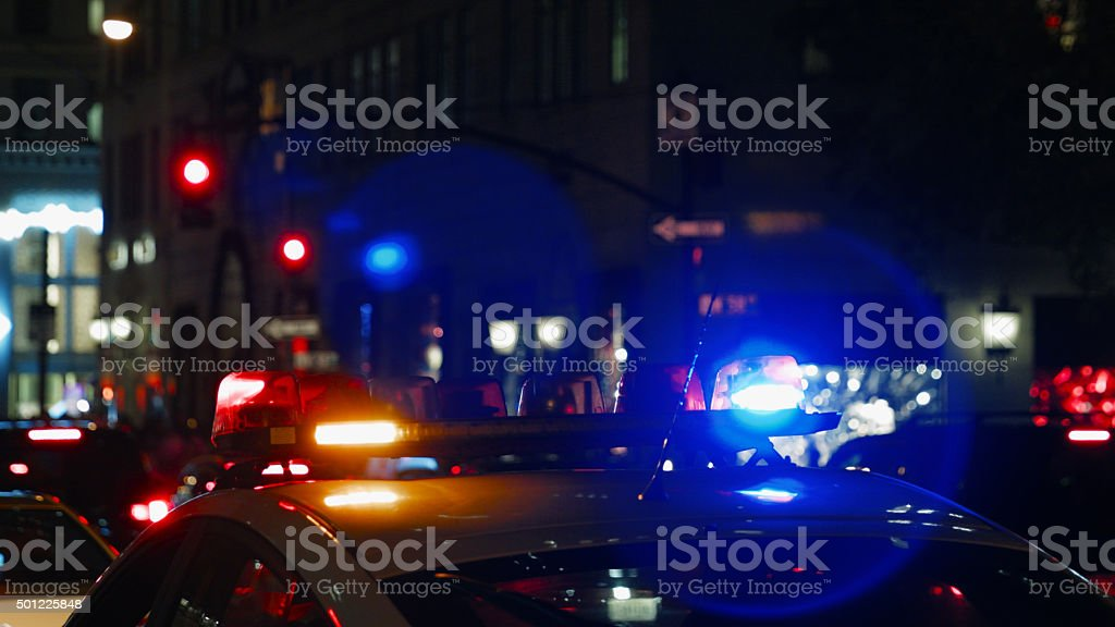 Police car with turned on siren at night street stock photo