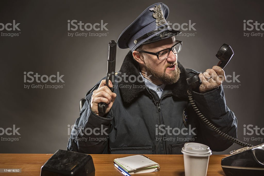 Police Chief Talking on the Phone with Gun in Hand royalty-free stock photo