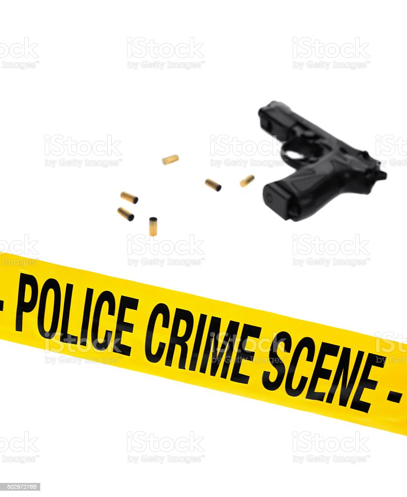 Police crime scene tape with hand gun and shell casings stock photo