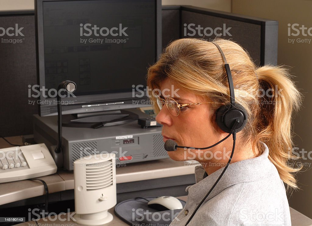 Police dispatcher sitting at a dispatch console stock photo