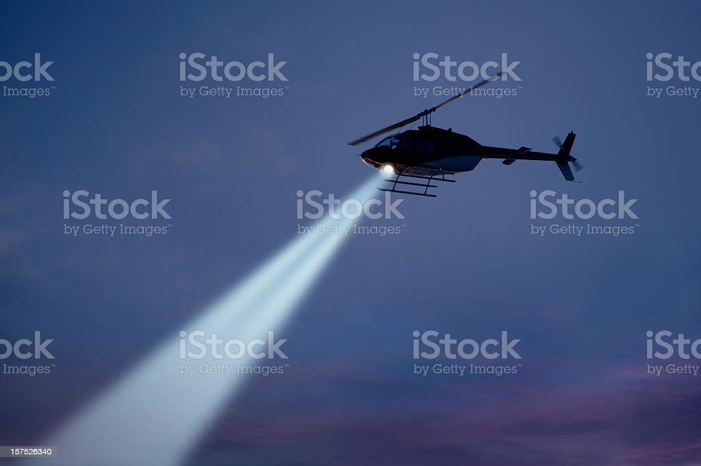 Police helicopter shining a light beam in the dark sky stock photo