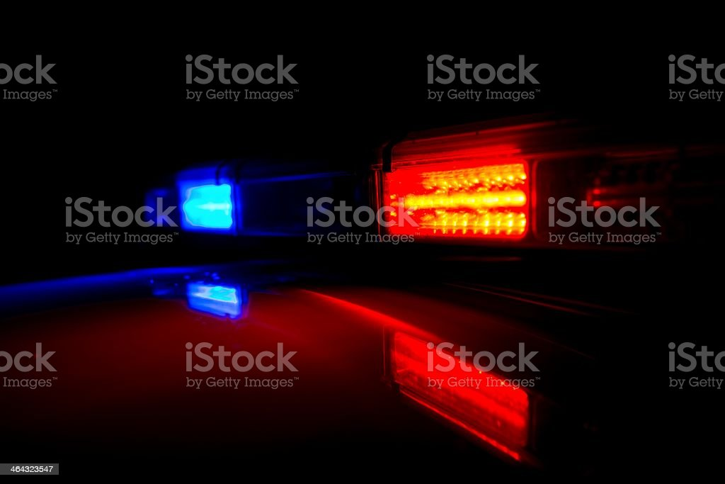 Police lights glow at night and reflect off of their roof stock photo