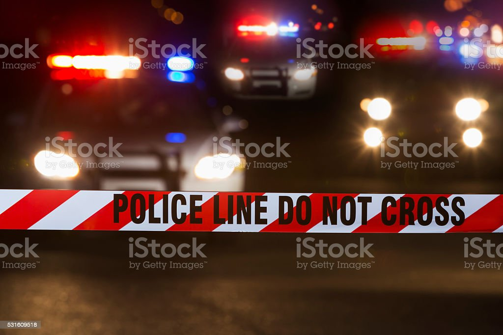Police Line Do Not Cross tape, street at night stock photo
