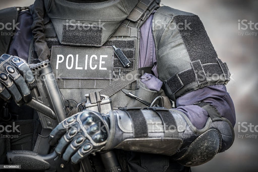 SWAT Police Officer Against Brick Wall stock photo