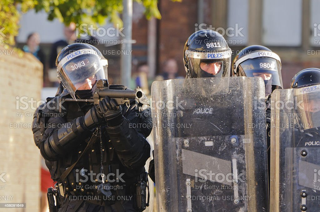 Police officer aims AEP (plastic bullet) gun at rioters stock photo