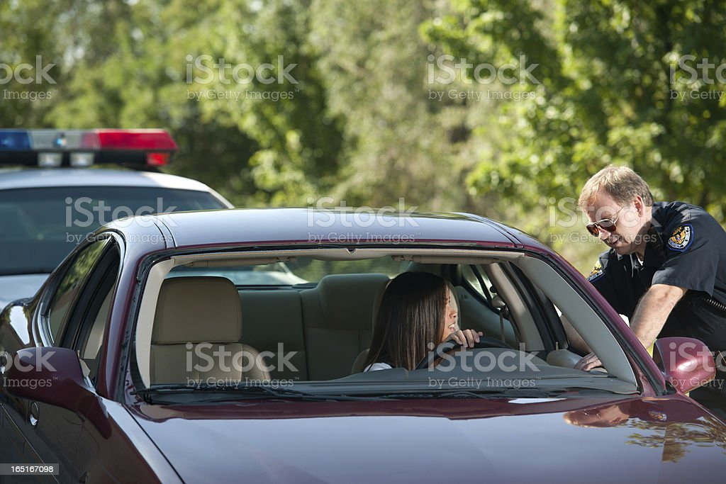 Police Officer Approaches Female Driver (Vertical) stock photo