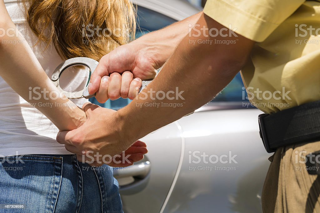 Police officer arresting a woman with handcuffs stock photo
