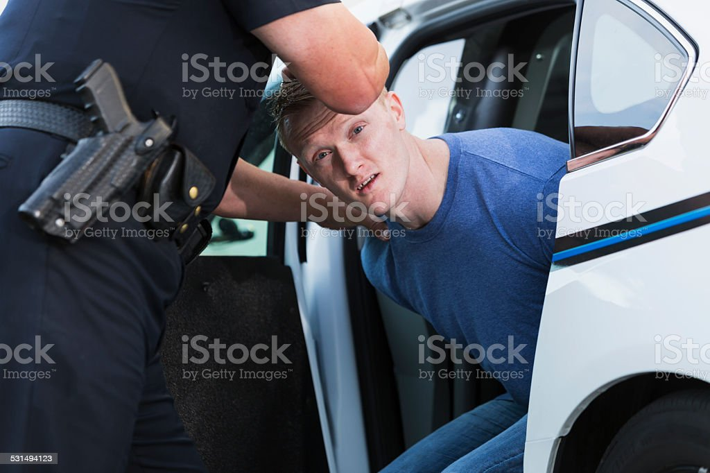 Police officer arresting a young man stock photo