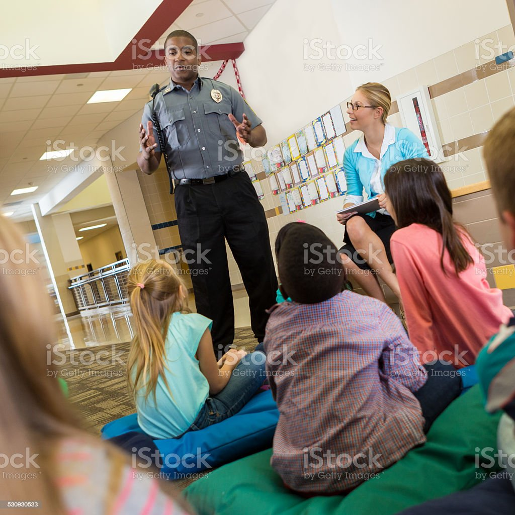 Police officer at school speaking to young students about safety stock photo