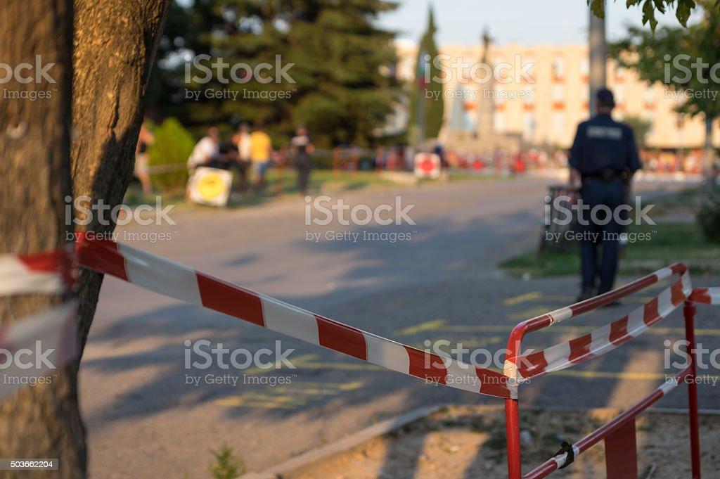Police officer behind red fence at srteet stock photo