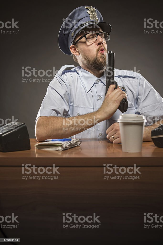 Police Officer Blowing the Top of his Gun in Satisfaction royalty-free stock photo