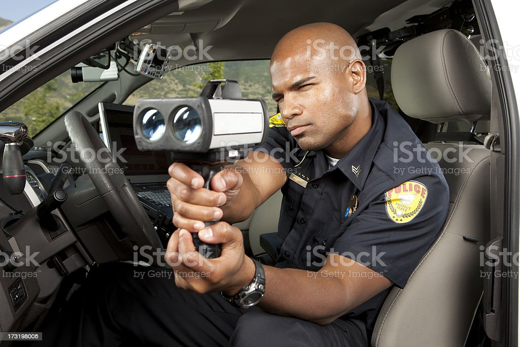 Police Officer checking vehicle speed with radar gun stock photo