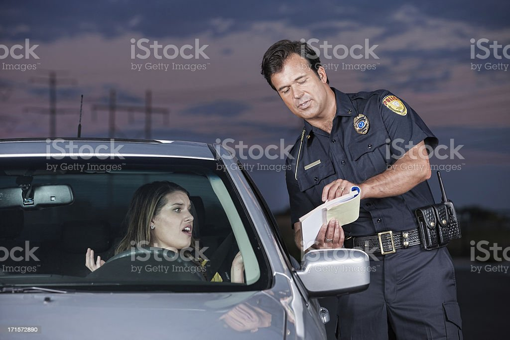 Police Officer Explaining Citation to Woman Driver stock photo