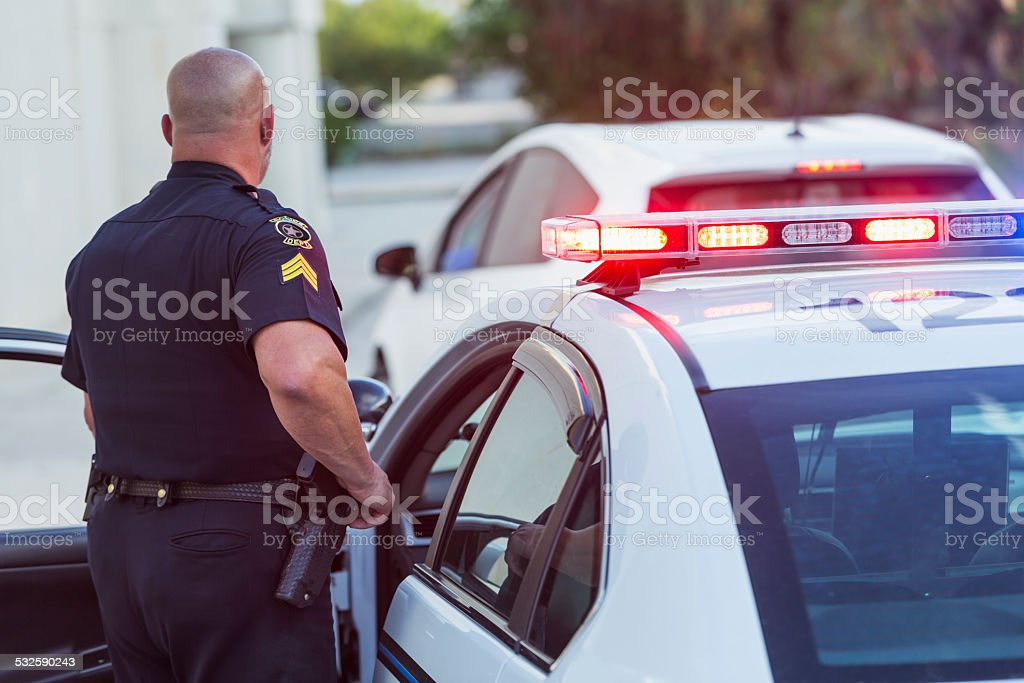 Police officer getting out of cruiser stock photo