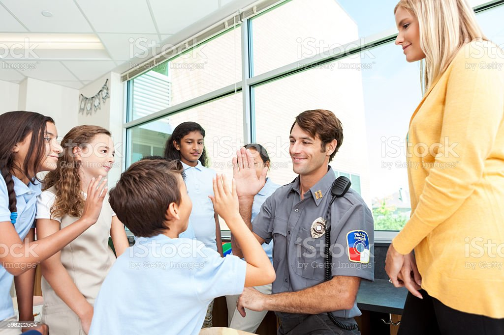 Police officer gives high five to elementary school student stock photo