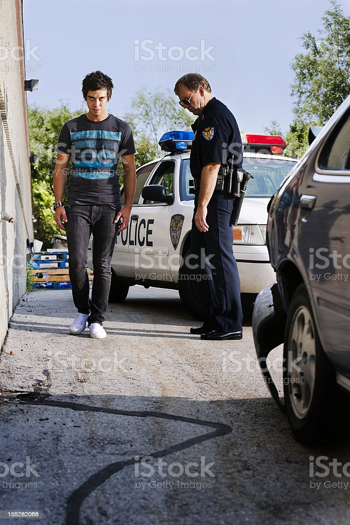 Police officer giving a man a field sobriety test stock photo