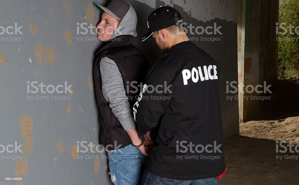 Police officer handcuffing young man against wall stock photo