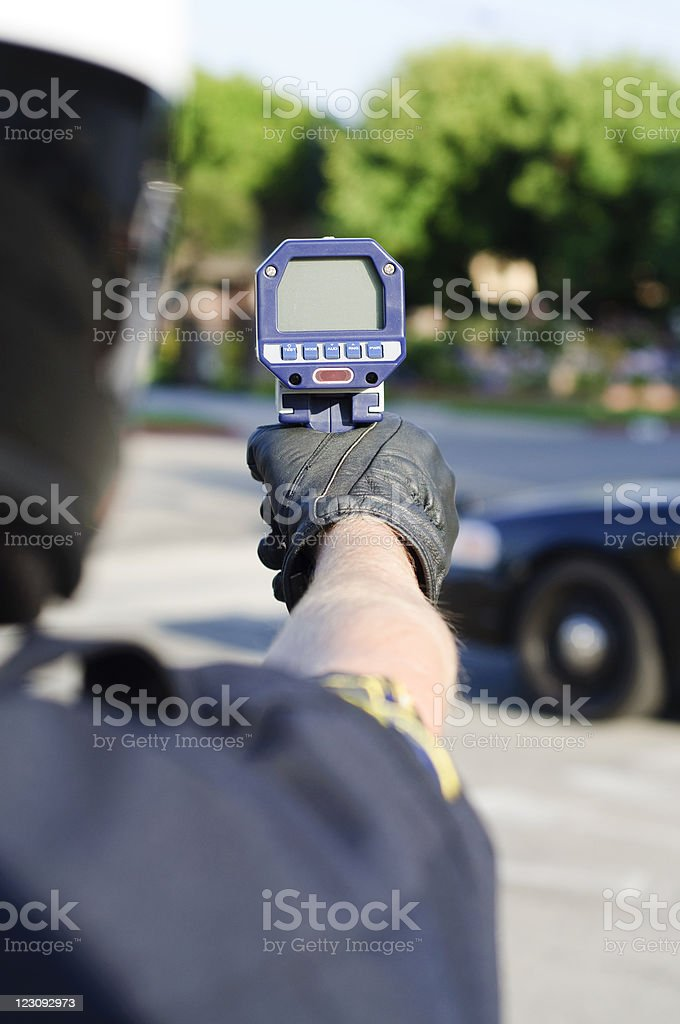 Police officer holding a radar gun pointing at the street stock photo