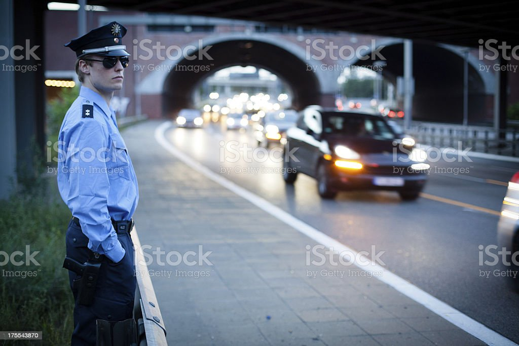 police officer in a blue uniform observe the city traffic stock photo