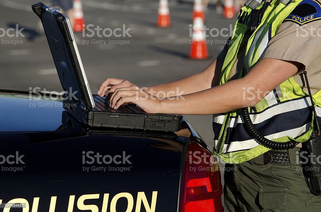 Police officer in reflective vest at laptop on back of car  stock photo