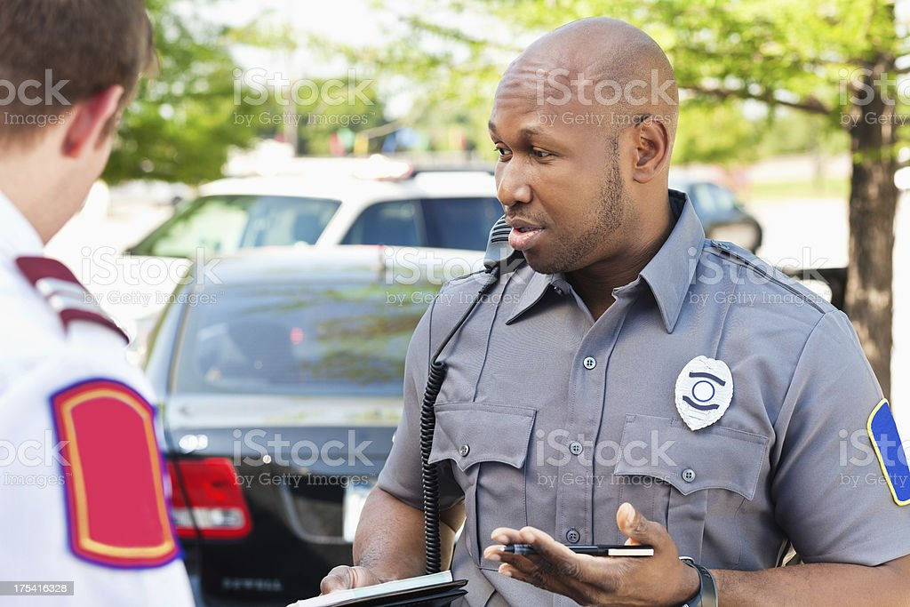 Police officer interogating people at an emergency scene stock photo