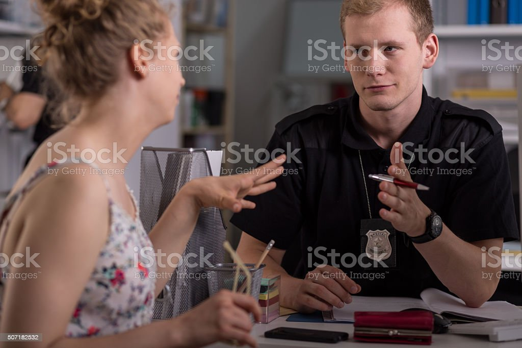Police officer interrogating woman stock photo