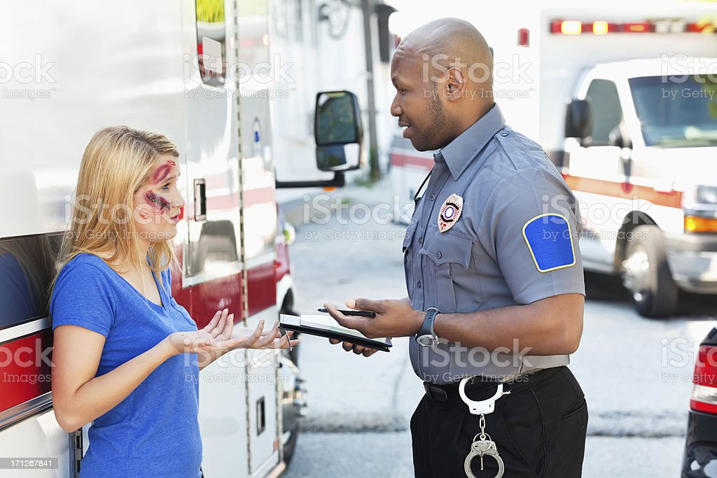 Police Officer Interviewing Witness at Accident Site stock photo