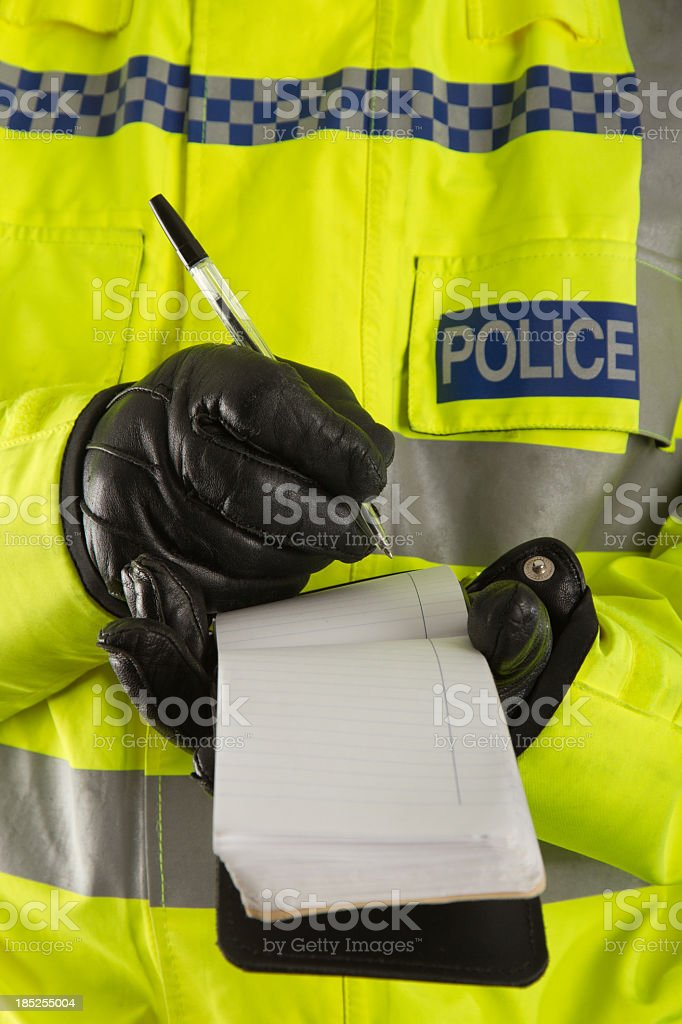 Police officer jotting down details in his notepad stock photo