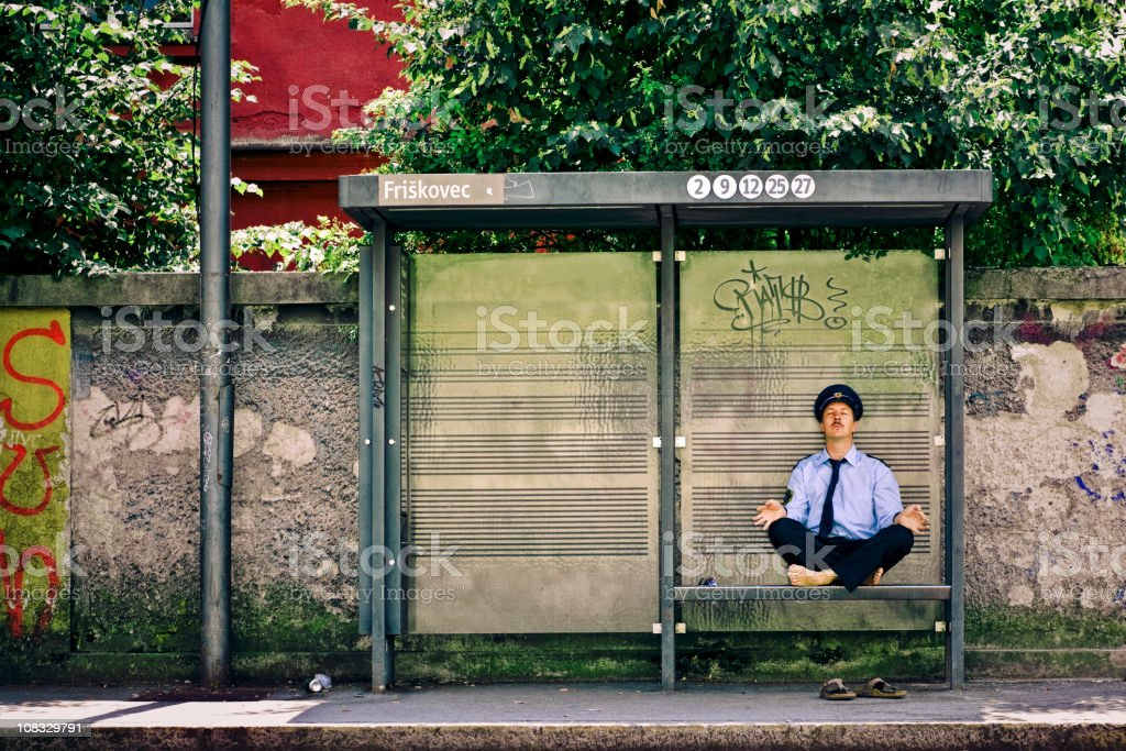 Police officer meditating on the bus station stock photo