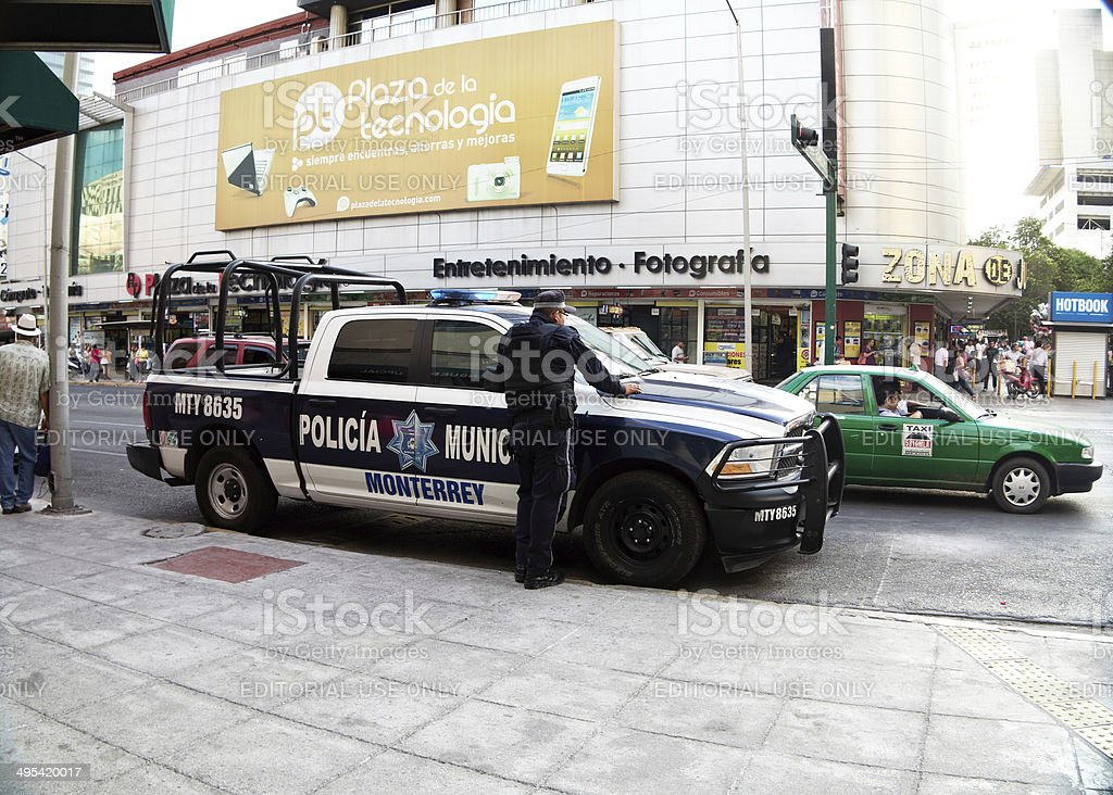 Police officer outside his truck on street in downtown Monterrey stock photo