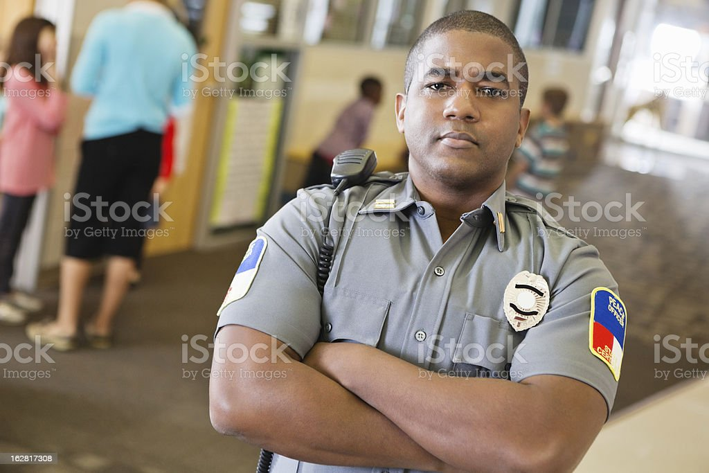 Police officer patrolling hallway in elementary school royalty-free stock photo