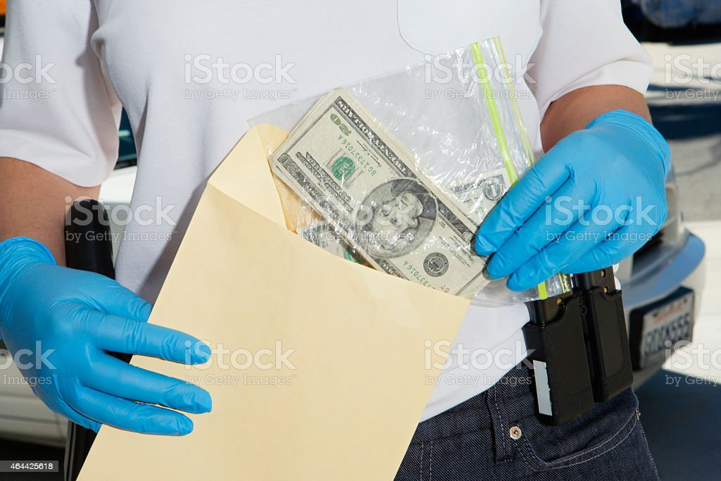 Police Officer Putting Money in Evidence Envelope stock photo