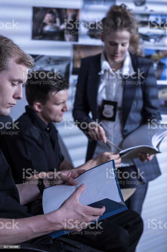 Police officer reading files stock photo