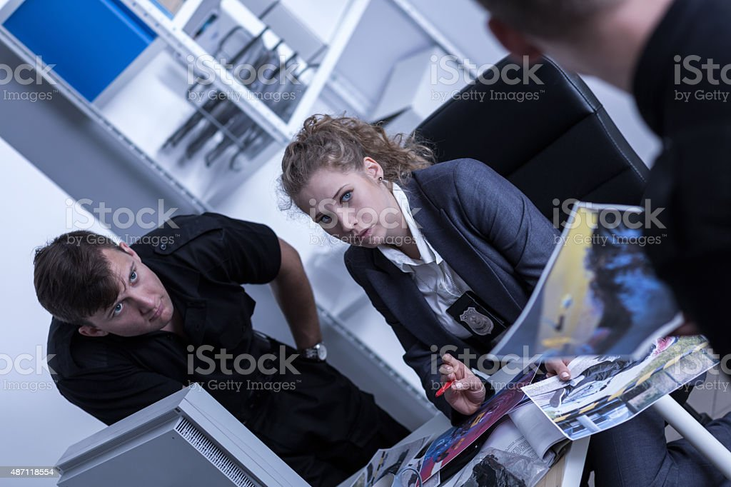 Police officer reviewing photos stock photo