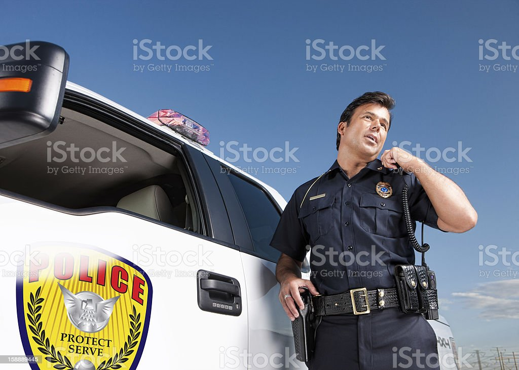 Police Officer Talking on Radio by Patrol Vehicle stock photo