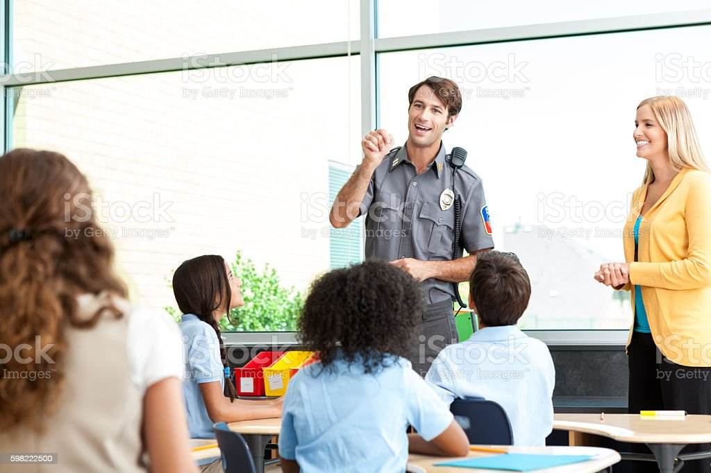 Police officer teaches class of children about safety. stock photo