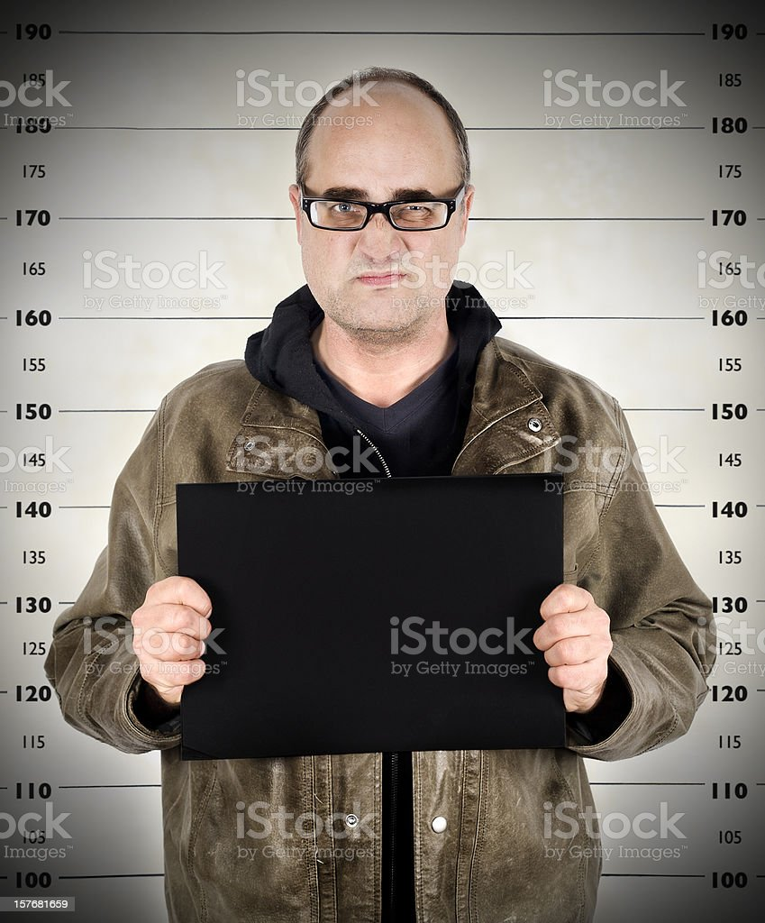 Police photo of arrested man with measuring scale in back royalty-free stock photo